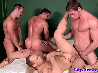 Muscled studs covering hunk in cum